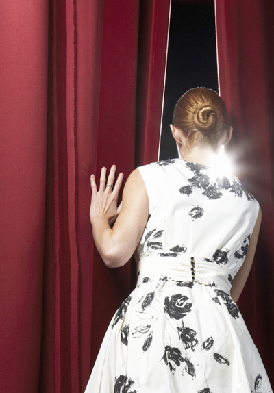 Woman looking at audience from behind stage curtain.
