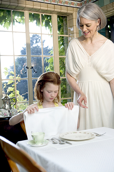 Mature mother standing by daughter (6-8) sitting at table, Dating, etiquette, manners, napkin, courtesy
