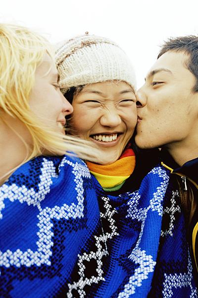 Young woman watching young man kissing woman on cheek, close-up