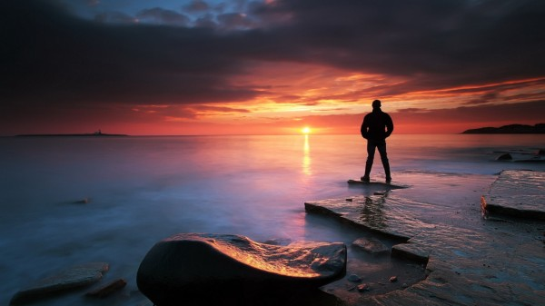 silhouette-of-a-man-at-a-rocky-shore-in-sunset-hd-wallpaper-516870